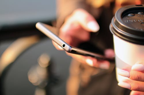 Hands Holding Coffee & Smartphone Sending Email